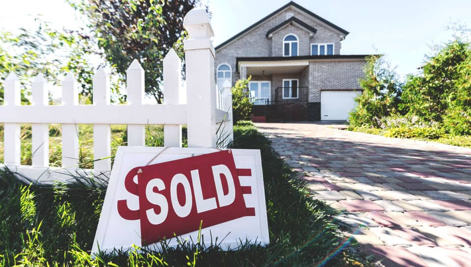 white picket fence house with sold sign